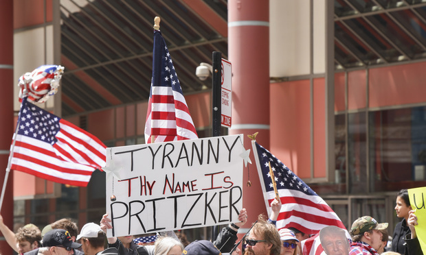 Chicago, Illinois / USA - May 1, 2020: Civil protest in Downtown Chicago against the restrictions placed upon the citizens by Governor J.B. Pritzker in front of the James R. Thompson Center. (Kevin Kipper/Shutterstock)