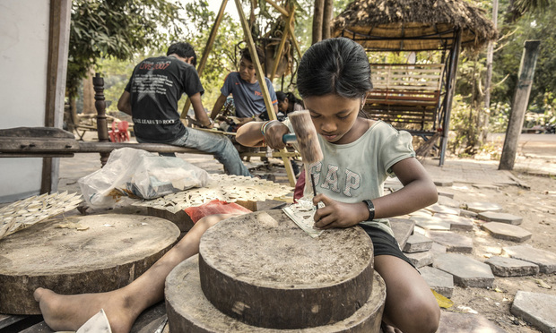 Girl working among other children outside a shop in an Angkor temple in the Seam Reap province. She is carving leather to produce beautiful works used for Shadow Puppetry or sold to tourists that visit the Angkor temples. Child labor in Cambodia is still very common.