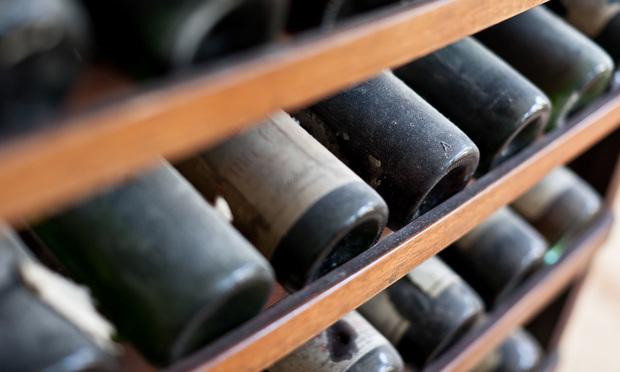 Dusty wine bottles/Photo by Dario Lo Presti/Shutterstock.com