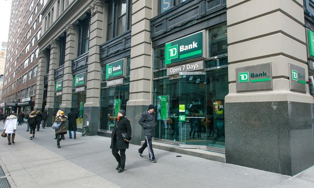 People walk by a TD Bank branch in Manhattan,New York.