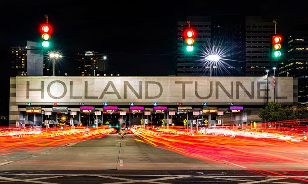 Holland Tunnel toll booth. Owned and operated by Port Authority, a joint venture between the U.S. states governments of NY and NJ, Holland Tunnel crosses Hudson River between Manhattan and Jersey City - Image by Shutterstock