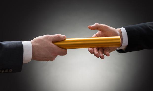 two businessmen passing a golden baton - Andrey Popov/Shutterstock.com