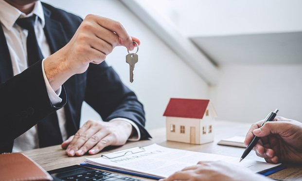 Estate agent giving house keys to client