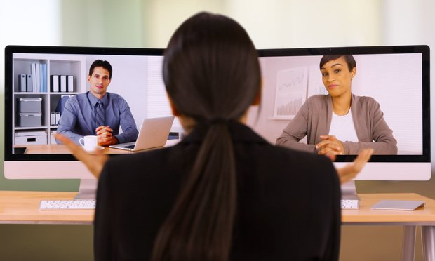 A young lawyer video chats with her co-workers.