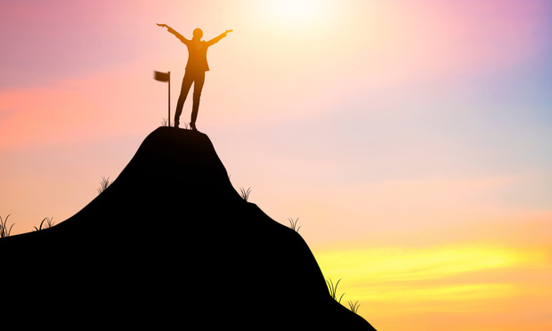 success and winner concept, silhouette of business women rising hands and flag on mountain- Onchira Wongsiri/Shutterstock