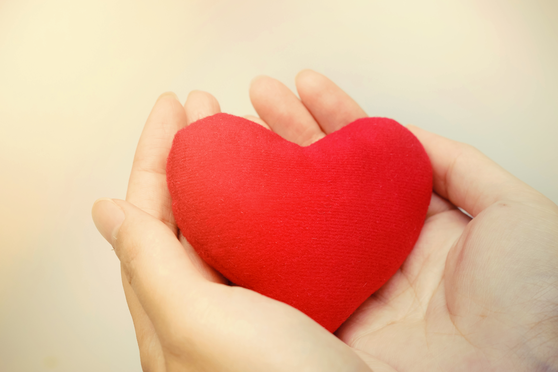 hands holding a red heart with warm light.