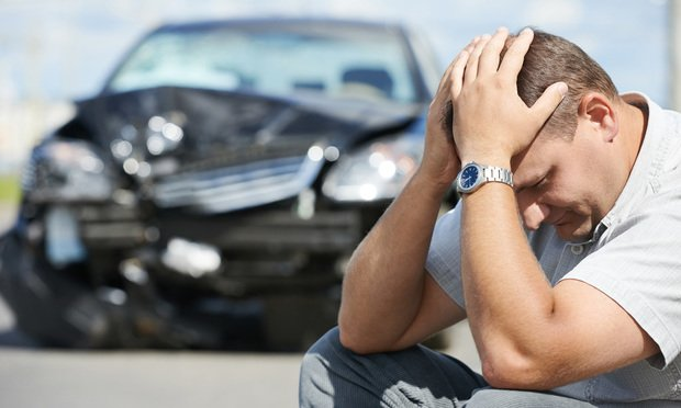 upset man in front of crashed car