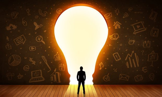 silhouette of man standing before giant light bulb cut-out in a wall