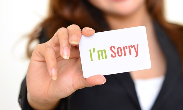 "Woman holding card that says, ""I'm Sorry"""