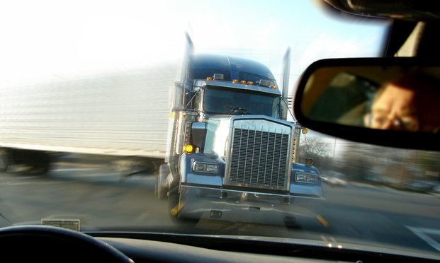 looking out a car's winshield at an oncoming truck