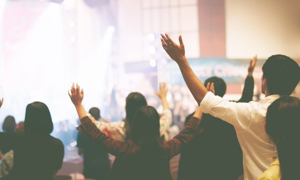 people raise arms at Christian music concert