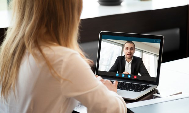 A professional woman and man talking via video chat