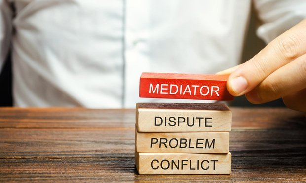 man stacking blocks on table that say mediator dispute problem conflict