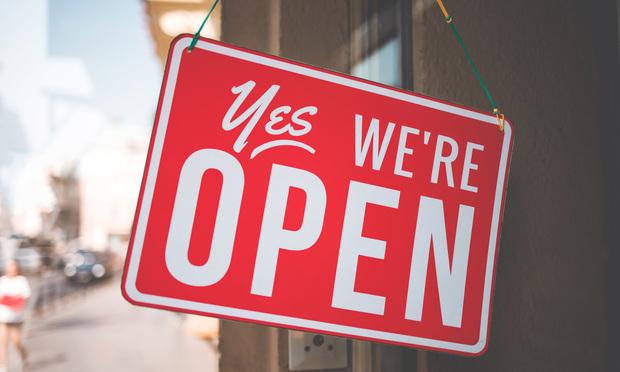 """red door sign says """"Yes, we're open."""""""