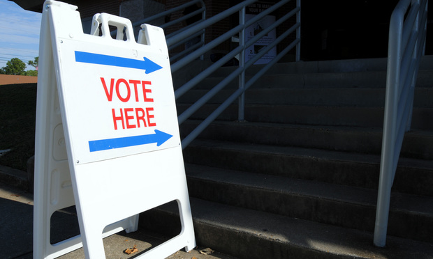 a-frame sign with arrows and 'vote here'