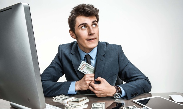 businessman puts stack of cash in his suit pocket