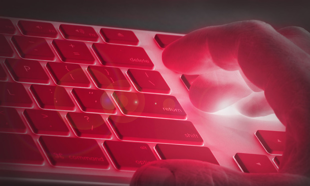person typing on a computer keyboard that is under red light