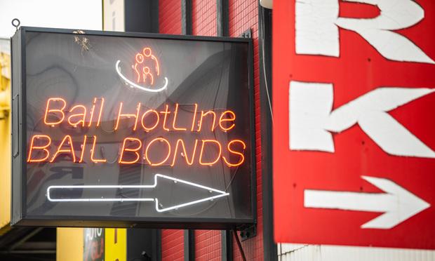 "neon sign that says ""bail hotline; bail bonds"""