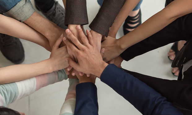 People of diverse races place their hands in a huddle