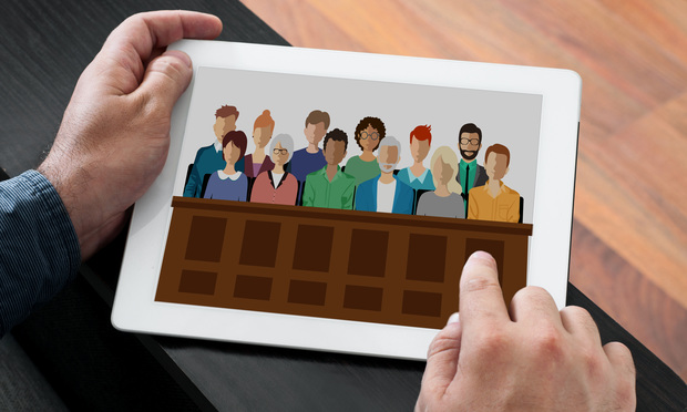 A man holds a tablet with a photo of a jury sitting in a jury box. Photo: Shutterstock