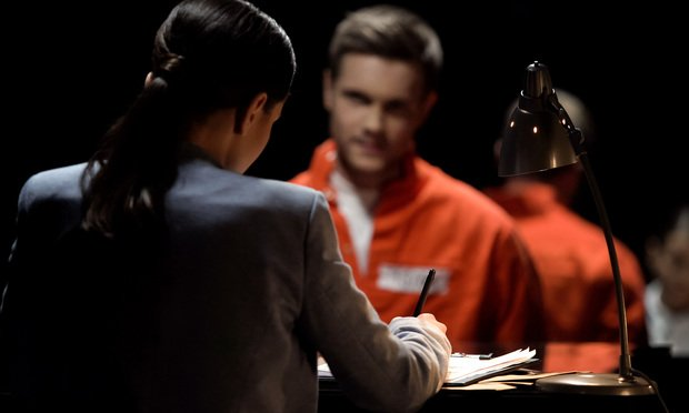 A criminal-defenendant in an orange jumpsuit sits and talks to a woman in a business suit. Photo: Motortion Films/Shutterstock