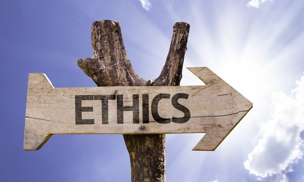 "A wooden sign with ""ethics"" written on it is nailed to a forked tree branch. Photo: Shutterstock"