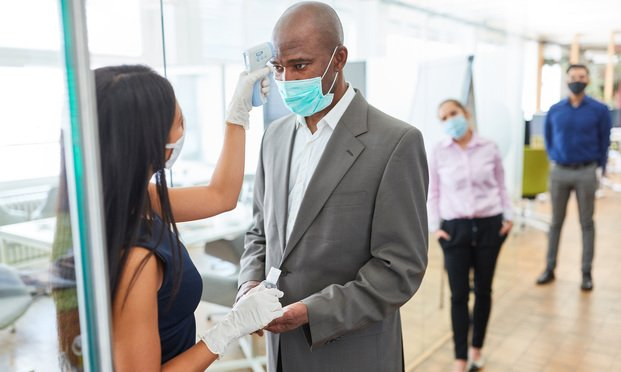 Businessman has his temperature checked entering an office. Photo: Shutterstock