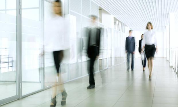 blurry business people walking down hallway