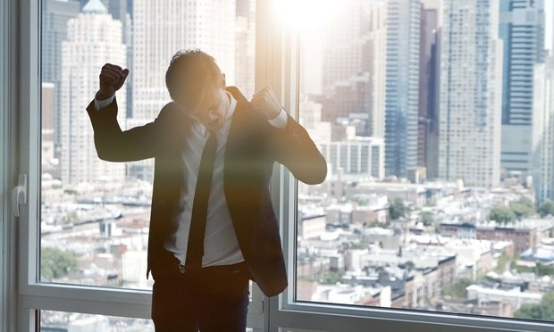 excited young caucasian businessman dancing cheerful in modern office. successful lifestyle portrait. silhouette of person background
