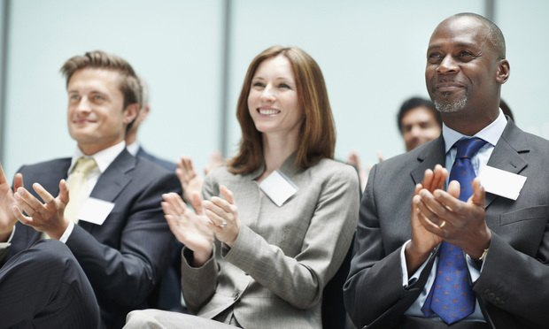 Group of confident corporate people applauding during business seminar. Smiling. Happy. Clapping. Proud.