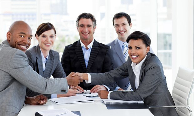 A diverse business group closing a deal in the office