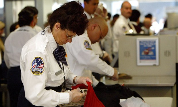 Transportation Security Administration screeners inspect passengers' bags at the international terminal of San Francisco International Airport. Photo credit: Getty Images