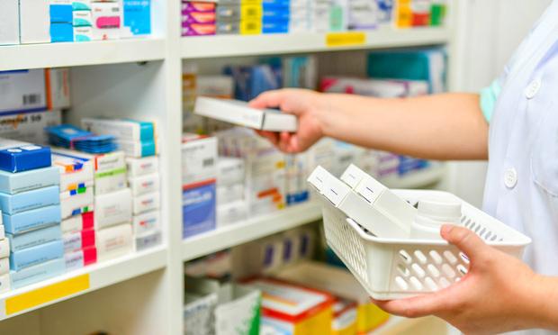 Pharmacist filling prescription in pharmacy drugstore.