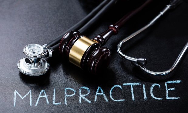 Malpractice Concept Showing Gavel And Stethoscope On Blackboard