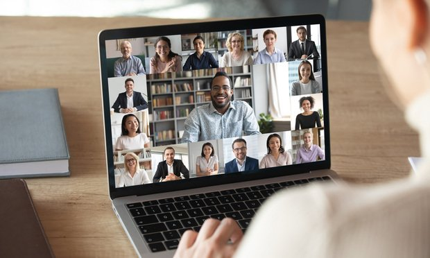 Back view of female employee speak talk on video call with diverse multiracial colleagues on online briefing, woman worker have Webcam group conference with coworkers on modern laptop at home Photo: by Shutterstock