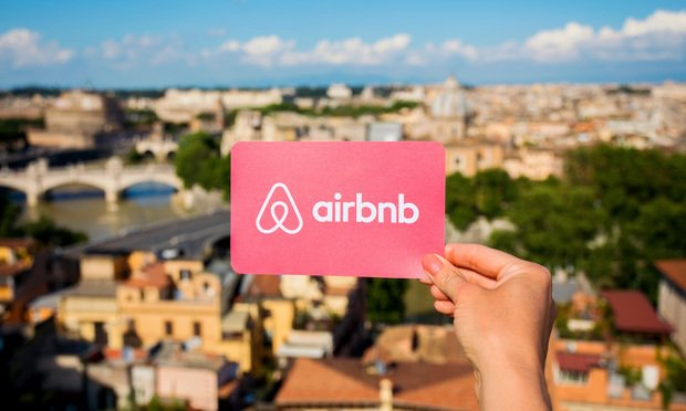 Airbnb logo held in front of a cityscape.