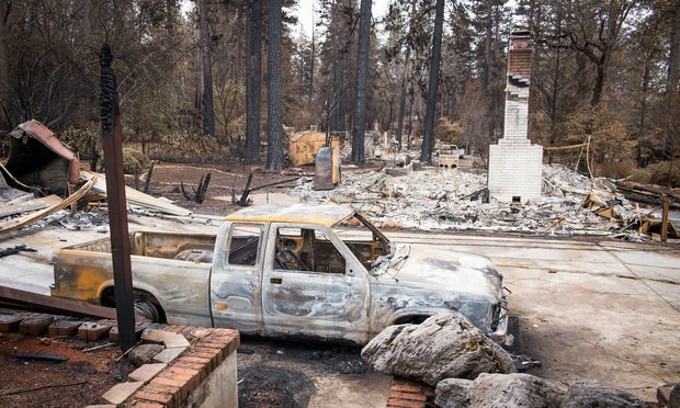 A burned-out vehicle is seen near destroyed homes in Paradise, California, U.S., on Monday, Nov. 26, 2018. The nation's deadliest wildfire in a century known as the Camp Fire that killed at least 85 people and burned over 14,000 homes has been fully contained after burning for more than two weeks, authorities said Sunday. (Photo: David Paul Morris/Bloomberg)