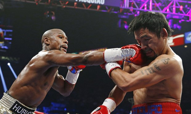 <i>Floyd Mayweather Jr., left, connects with a right to the head of Manny Pacquiao, from the Philippines, during their welterweight title fight in Las Vegas. Mayweather was one of the hottest topics on Facebook in 2015. Photo: John Locher/AP <i />