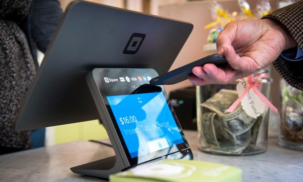 A customer uses an Apple Inc. iPhone to make a payment on a Square Inc. device in San Francisco, California, U.S., on Tuesday, March 27, 2018. The mobile payment market is anticipated to grow reaching a market value of $4,574 billion by 2023, according to data provided by Allied Market Research (AMR). The growth projections are attributed to an increasing demand for hassle-free purchase of goods and services, as well as an increased preference of consumers toward digital and cashless payments. Photographer: David Paul Morris/Bloomberg