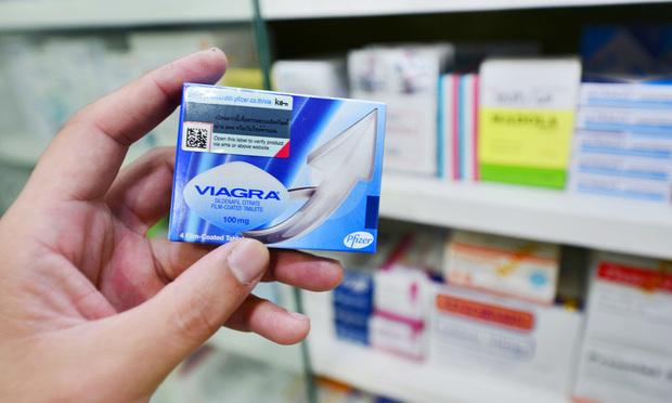 Person holding Viagra box in store aisle