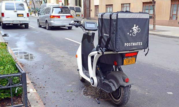 A Scooter with a Postmates courier bag on the back. (Photo: Shutterstock.com).