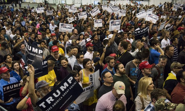 Attendees hold signs and listen as Donald Trump, presumptive Republican presidential nominee, not pictured, speaks during a campaign event at the San Jose Convention Center in San Jose, California, U.S, on Thursday, June 2, 2016. House Speaker Paul Ryan said he'll vote for Trump for president in November, ending a standoff over whether the party's top elected official would back its White House contender. Photographer: David Paul Morris/Bloomberg