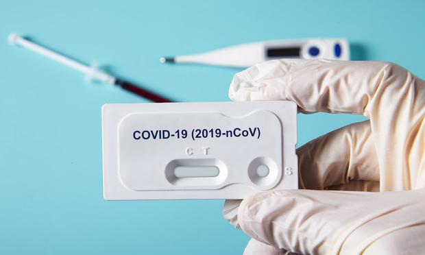 Doctor holding a test kit for viral disease COVID-19 2019-nCoV. Lab card kit test for viral novel coronavirus sars-cov-2 virus