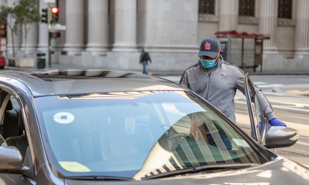 Uber driver Edward Nkansnh on California street in San Francisco on April 3, 2020. Nkansnh has suffered substantially less riders, instead replacing it with Uber Eats food delivery. (Photo: Jason Doiy/ALM)