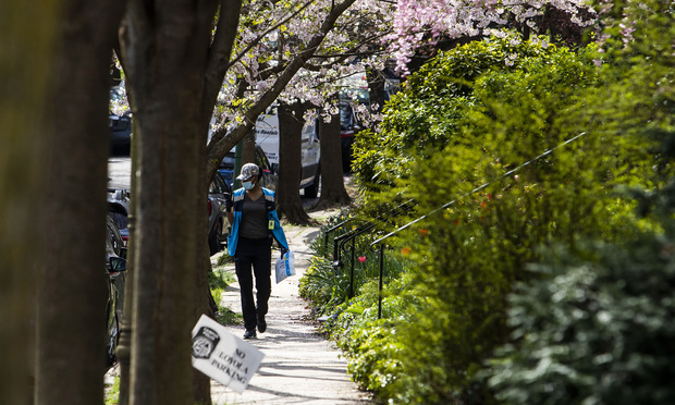 An Amazon Prime delivery person walks through a neighborhood wearing a mask to protect against coronavirus in Baltimore, MD, on April 5, 2020. Photo: Diego M. Radzinschi/ALM