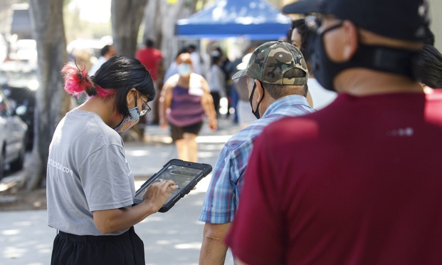 "A YMCA youth ambassador conducts a Census 2020 interview during a community food distribution at a YMCA location in Los Angeles, California, U.S., on Wednesday, Aug. 12, 2020. The YMCA-LA is sending ""youth ambassadors"" to 10 Grab & Go locations in diverse communities this week to encourage participation in this year's U.S. Census, NBC reports. Photographer: Patrick T. Fallon/Bloomberg"