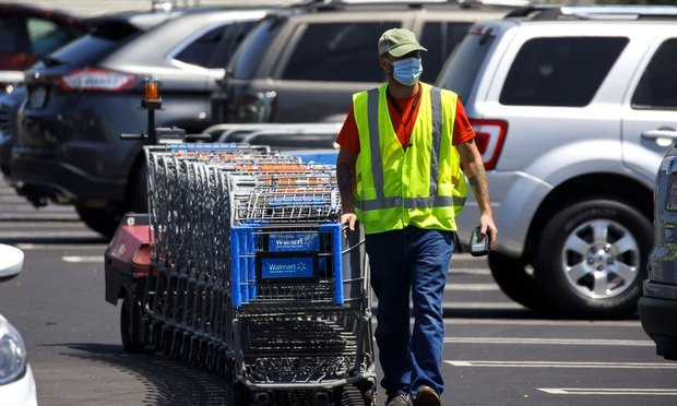 An employee wearing a protective mask pulls shopping carts at a Walmart store in Lakewood, California, U.S., on Thursday, July 16, 2020. Walmart Inc. will require customers to wear masks in all of its U.S. stores to protect against the coronavirus, an admission that the nation's pandemic has reached new heights and setting up potential confrontations with customers who refuse to don them. Photo: Patrick T. Fallon/Bloomberg