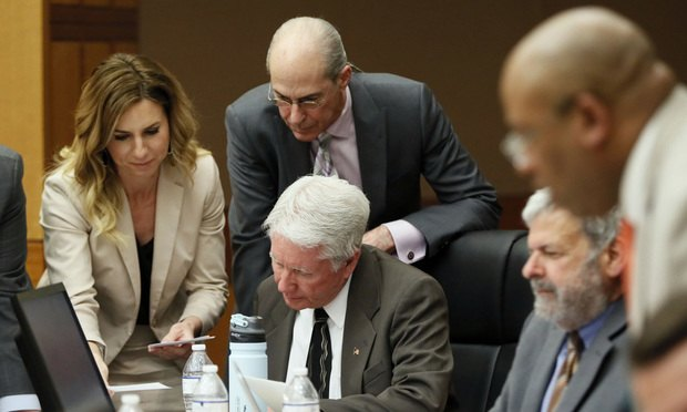 Tex McIver (seated) is surrounded by attorneys as they review questions from the jury for witness Annie Anderson on Thursday. (Pool photo: Bob Andres/AJC)