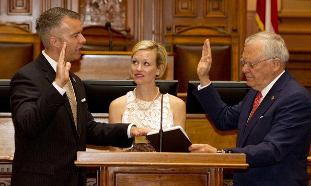 "E. Trenton ""Trent"" Brown III gets sworn in by Gov. Nathan Deal. Holding the Bible is Trent's wife, Jill. (Photo: John Disney/ALM)"