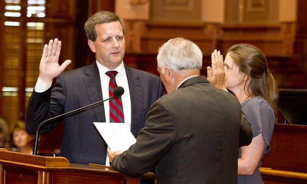 Judge Charlie Bethel (left) gets sworn in by Gov. Nathan Deal to the Georgia Supreme Court with his wife, Lynsey, watching. (Photo: John Disney/ALM)
